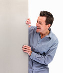 Excited mature man looking at blank board against white