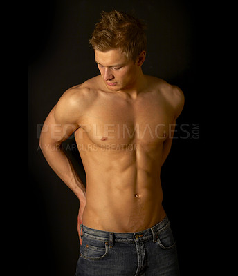 Buy stock photo Studio shot of a muscular bare-chested male model isolated on black