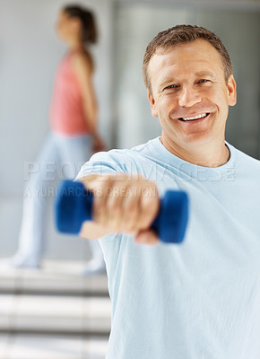 Buy stock photo Portrait of a happy middle aged man working out with a dumbbell at the gym