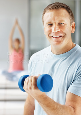 Buy stock photo Portrait of a smiling handsome guy working out with a dumbbell at the gym