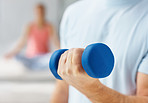 Closeup mid section of a man working out with a dumbbell