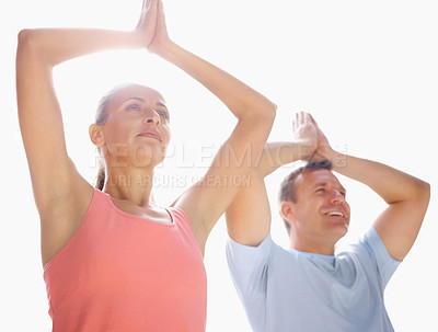 Buy stock photo Portrait of a happy couple practicing yoga together against white , hands joined above head