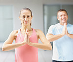 Smiling woman practicing yoga with a man at the back