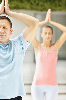 Buy stock photo Portrait of a spiritual guy practicing yoga with a woman at the back