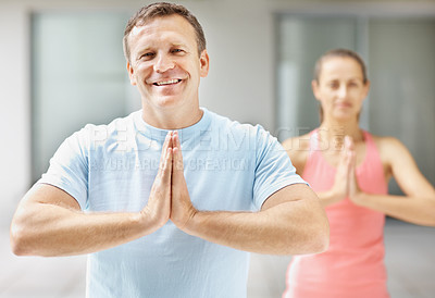Buy stock photo Fit and smiling man practicing yoga with a woman at the gym