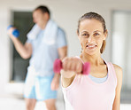 Happy woman using a dumbbell at the gym with man at the back