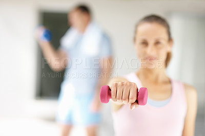Blur image of a female working out with a dumbbell at the gym