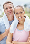 Man and woman with towel around their necks after a workout