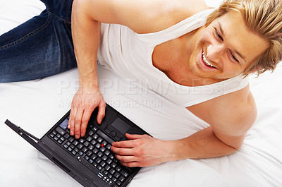 Buy stock photo Young guy browsing the internet from his bed.