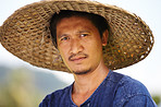 Portrait of a rice farmer in Thailand wearing a traditional hat