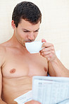 Shirtless man having tea while reading newspaper