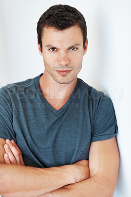 Buy stock photo Portrait of confident young man leaning against the wall with arms crossed