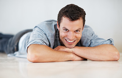 Buy stock photo Portrait of relaxed young man lying on floor with chin on hands