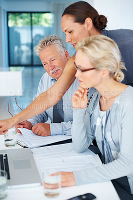 Buy stock photo Three business people discussing  project while using laptop in office