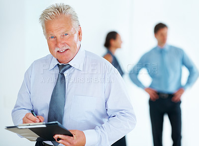 Buy stock photo Portrait of senior business man writing notes with colleagues in background