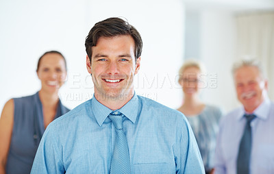 Buy stock photo Portrait of young business man smiling with colleagues in background