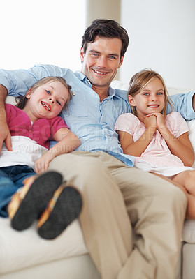 Buy stock photo Portrait of handsome middle aged man with daughters relaxing on sofa