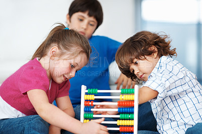 Buy stock photo Young little children using abacus at home