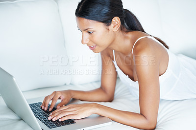 Buy stock photo Beautiful woman using laptop while lying on couch