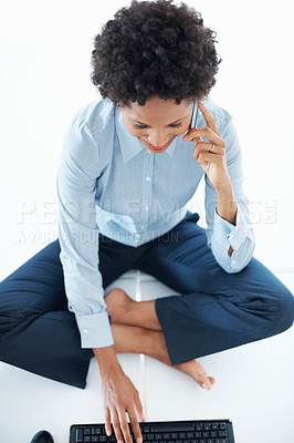 Buy stock photo High angle view of happy business woman taking on cellphone while using computer