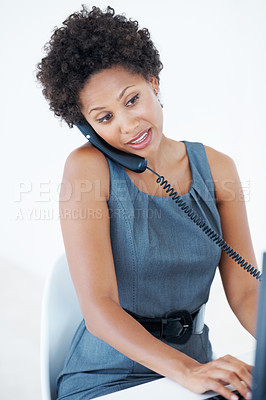 Buy stock photo Busy African American female executive talking on phone while looking at computer