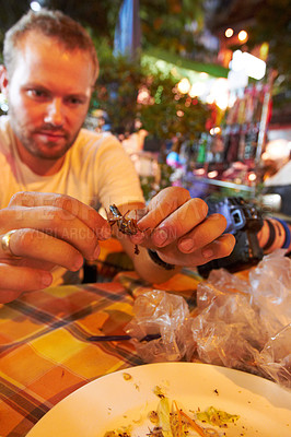 Buy stock photo Tourist tearing at the hind leg of a fried grasshopper