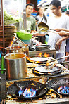 Chefs at a Thai streetmarket preparing food