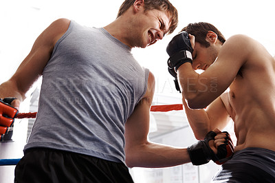 Buy stock photo Cropped shot of two martial artists sparring in the ring