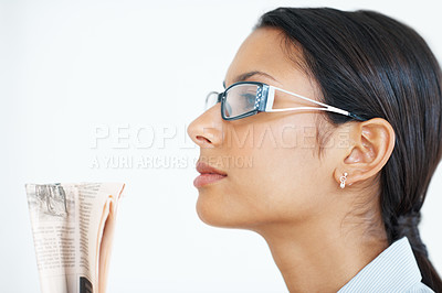 Buy stock photo Side view of business woman in glasses holding newspaper while looking at copyspace