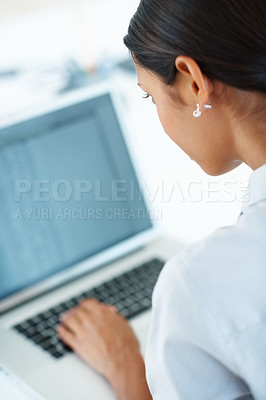 Buy stock photo Rear view of business woman busy using laptop at office desk