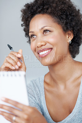 Buy stock photo Thoughtful young woman smiling while writing in notepad