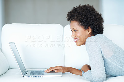 Buy stock photo Young woman using laptop while lying on couch