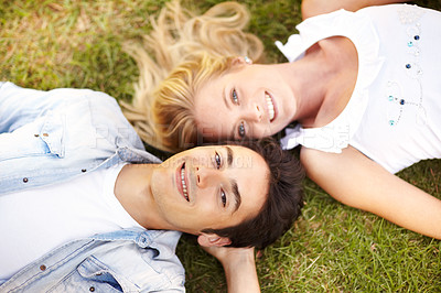 Buy stock photo Young couple lying head to head on a grass patch