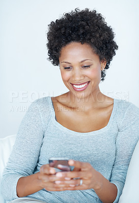 Buy stock photo Beautiful African American woman texting friend while sitting on couch