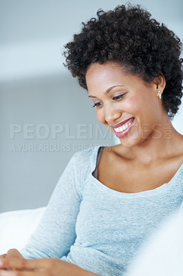Buy stock photo African American woman smiling while sitting on couch