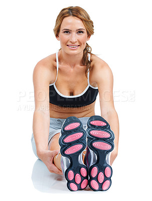 Buy stock photo A beautiful health-conscious young woman stretching out her legs while isolated on white