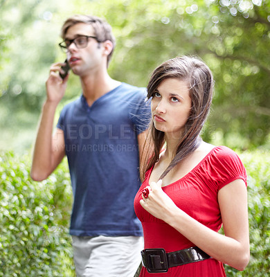 Buy stock photo Annoyed looking young woman walking next to her boyfriend in a park, while he chats on his cellphone