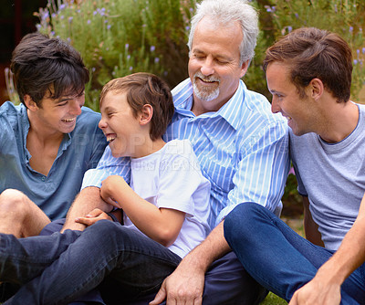 Buy stock photo Father and sons laughing with one another sitting on a lawn