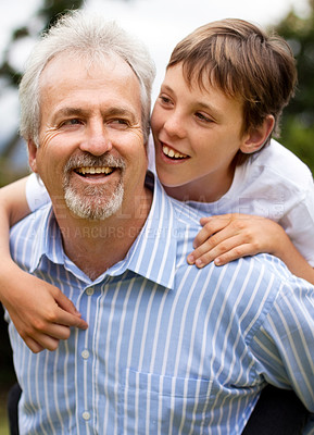 Buy stock photo Happy mature father giving his son a piggyback ride outdoors