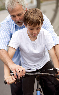 Buy stock photo Young boy learning how to ride a bicycle with his father's help