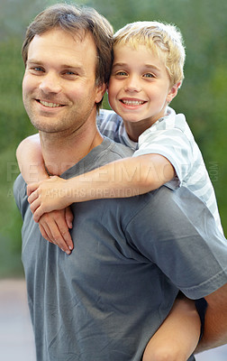 Buy stock photo Shot of a happy father giving his son a piggyback ride