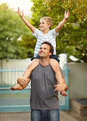 Buy stock photo Young boy on his fathers shoulders raising his hands in the air