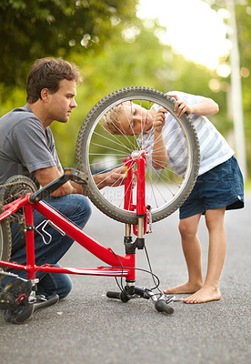 Buy stock photo Young father and son fixing a bicycle tyre puncture