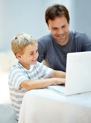 Buy stock photo Young boy on his laptop with his father next to him
