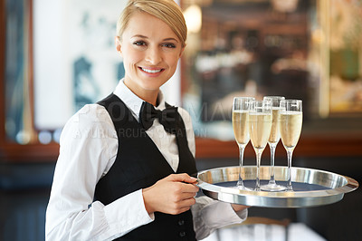 Buy stock photo Friendly waitress holding up a tray of champagne glasses in her hands at a celebration party