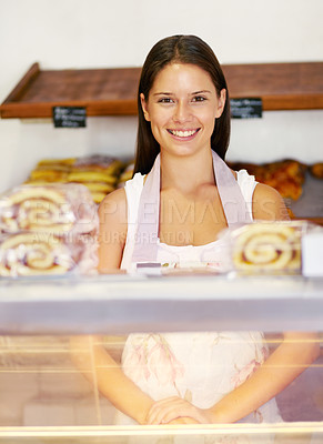 Buy stock photo Smiling young baker standing happily behind her serving counter - portrait
