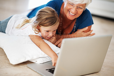 Buy stock photo Cheerful senior woman with little granddaughter lying on floor using laptop