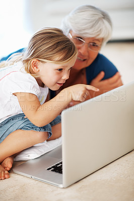 Buy stock photo Beautiful little girl using laptop with grandmother while sitting on floor