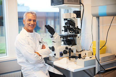 Buy stock photo Confident male researcher sitting in front of microscope at a laboratory