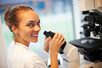 Happy young female researcher with microscope